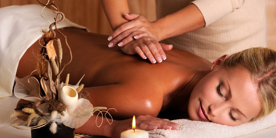Woman Experiencing A Massage Therapy In A Well Known Massage Centre By A Professional Massage Therapist.